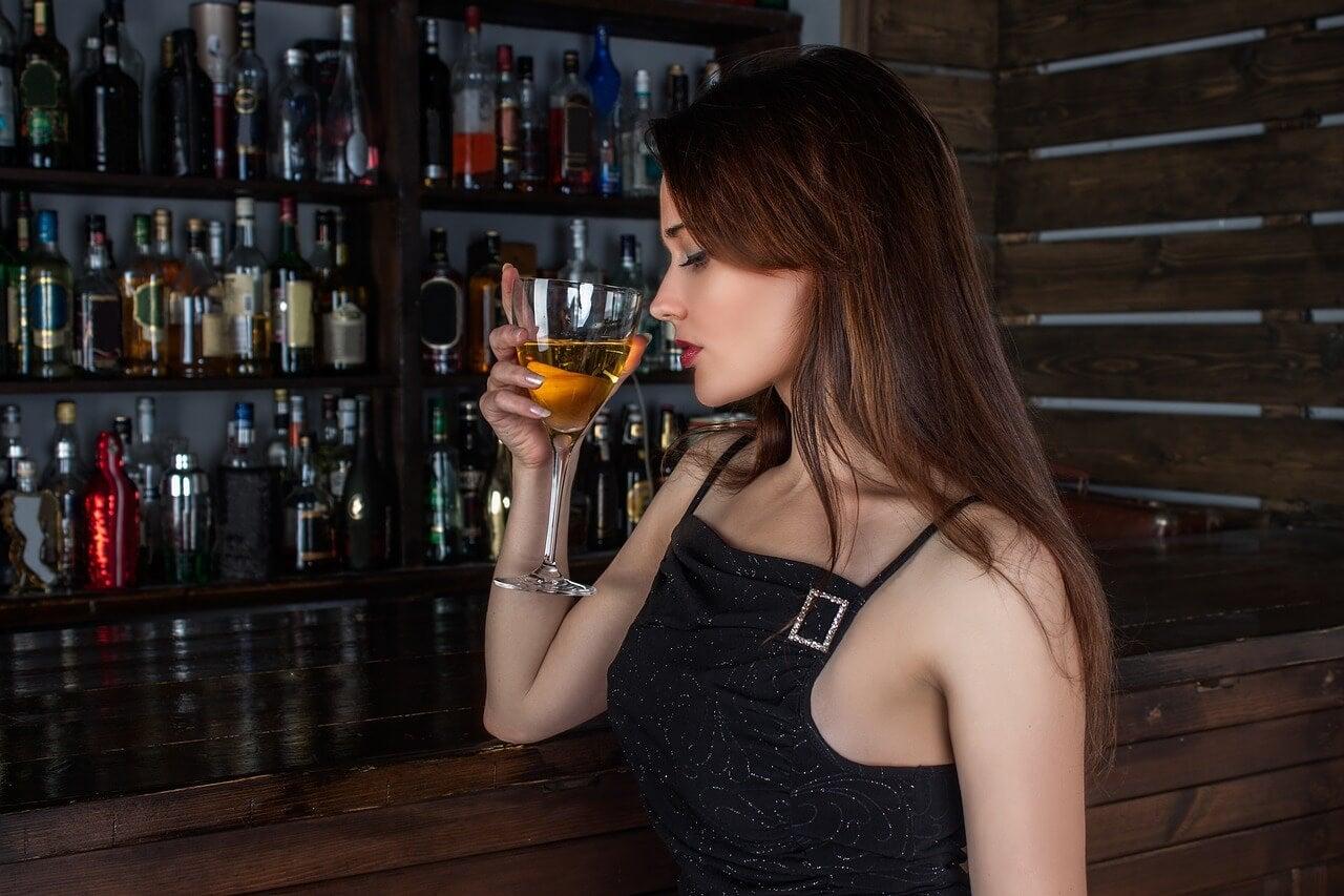 Mujer toma alcohol.