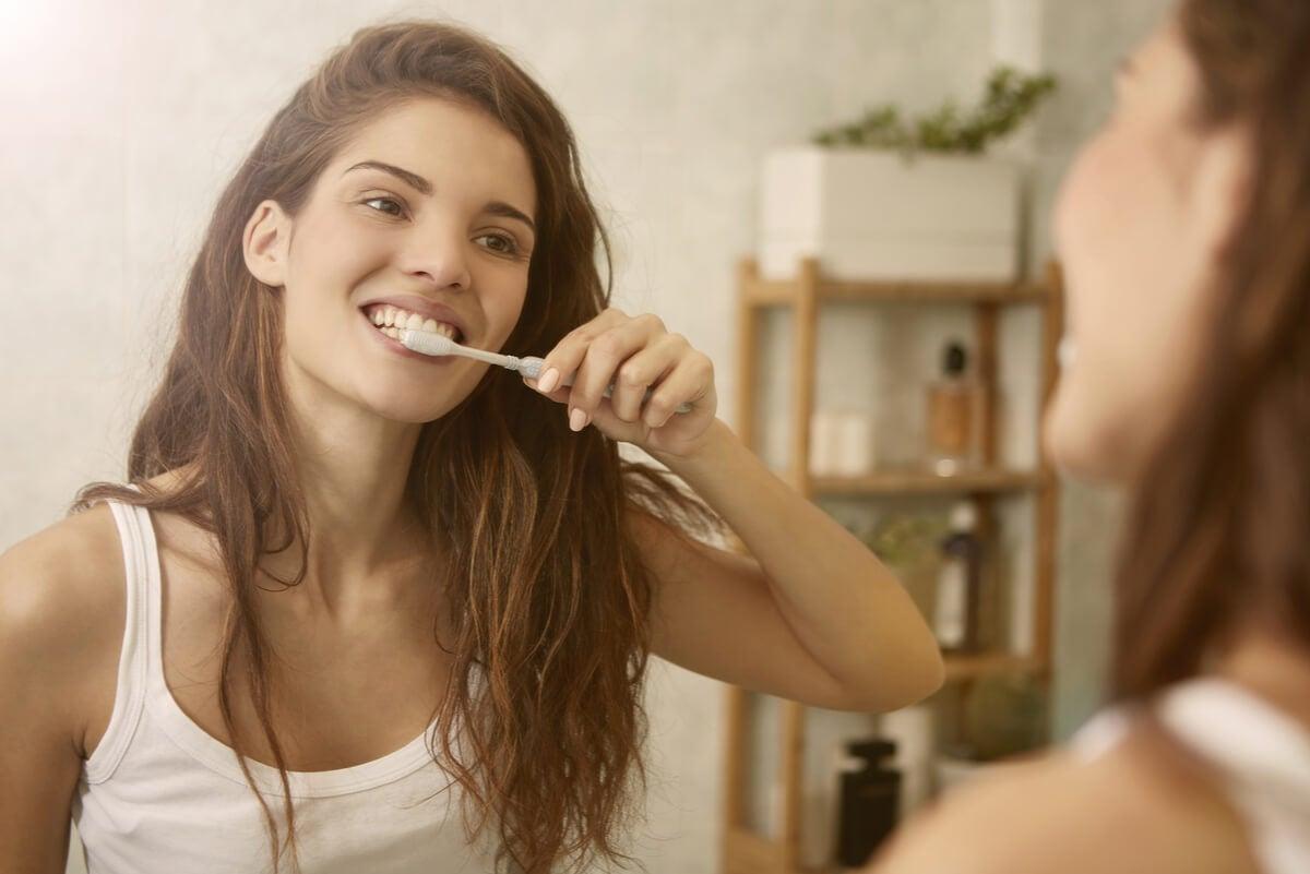 Mujer cepilla sus dientes por mal aliento.