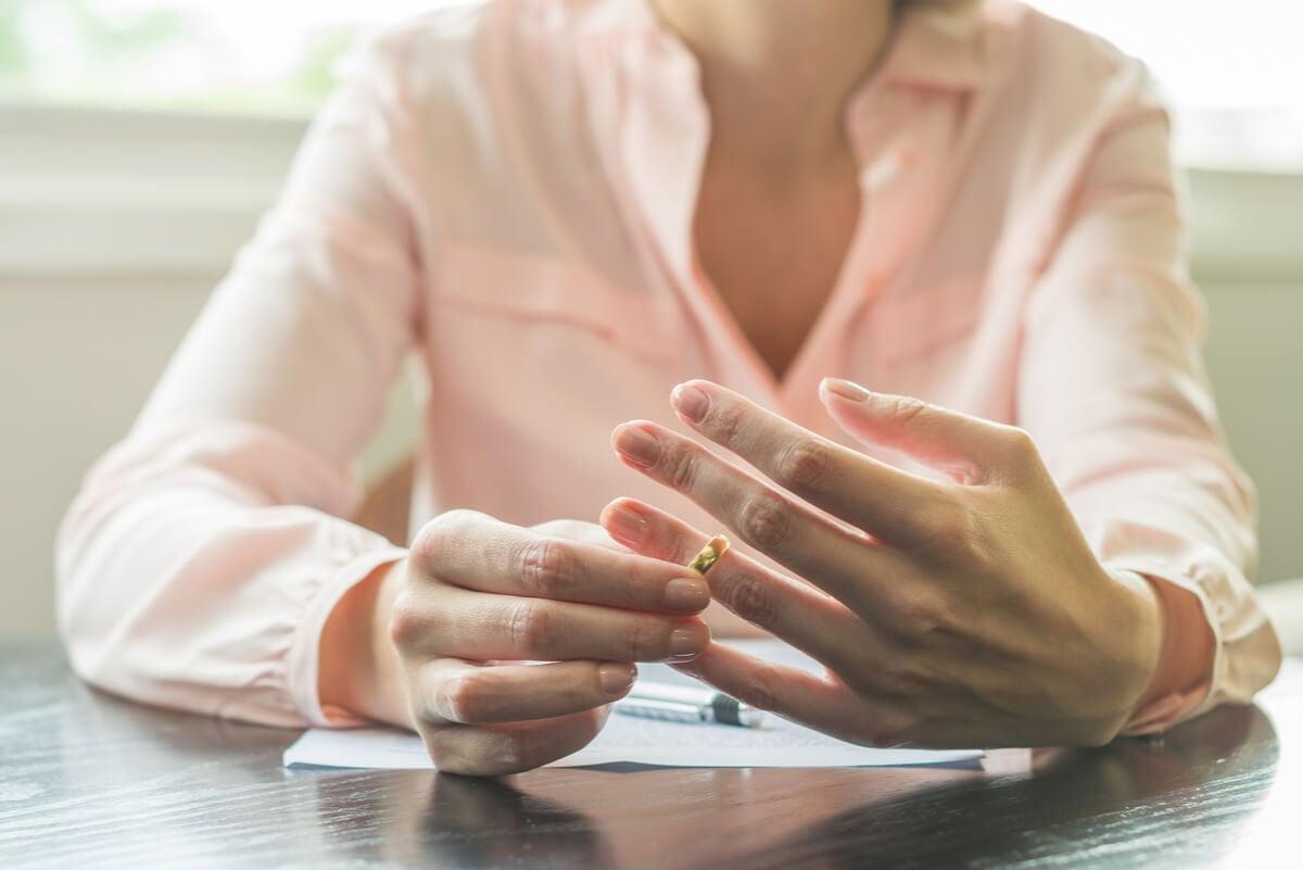 Ruptura de divorcio, una mujer quita el anillo de matrimonio de su mano.