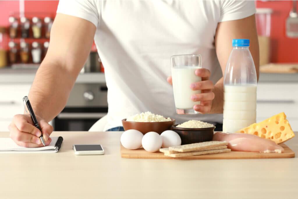 Hombre elabora dieta anotando.