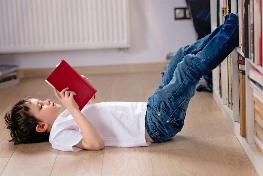 Niño lee acostado.