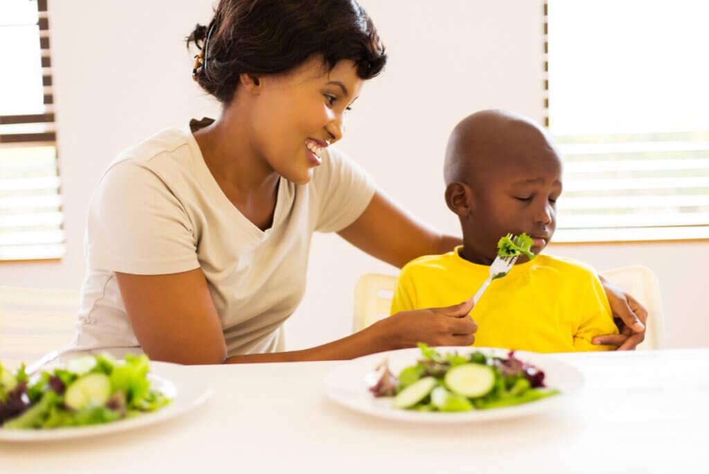 Madre ofrece comida a niño que la rechaza.
