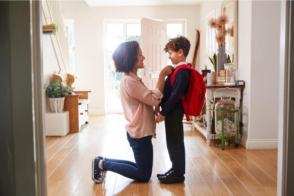 Madre mira a los ojos a niño que comienza la escuela.