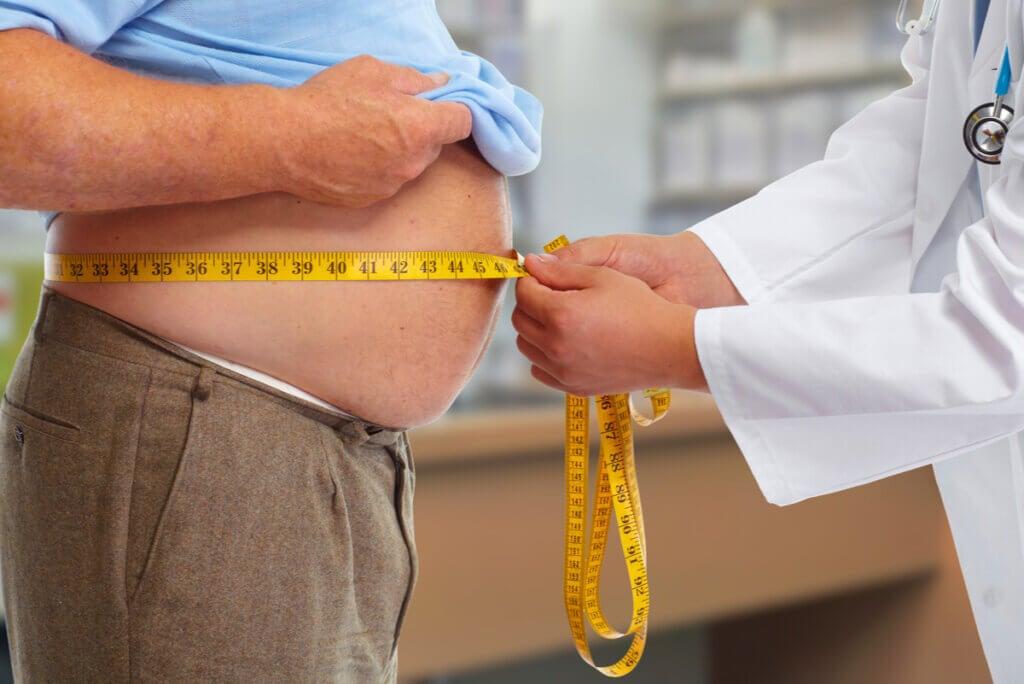 Médico mide circunferencia abdominal.