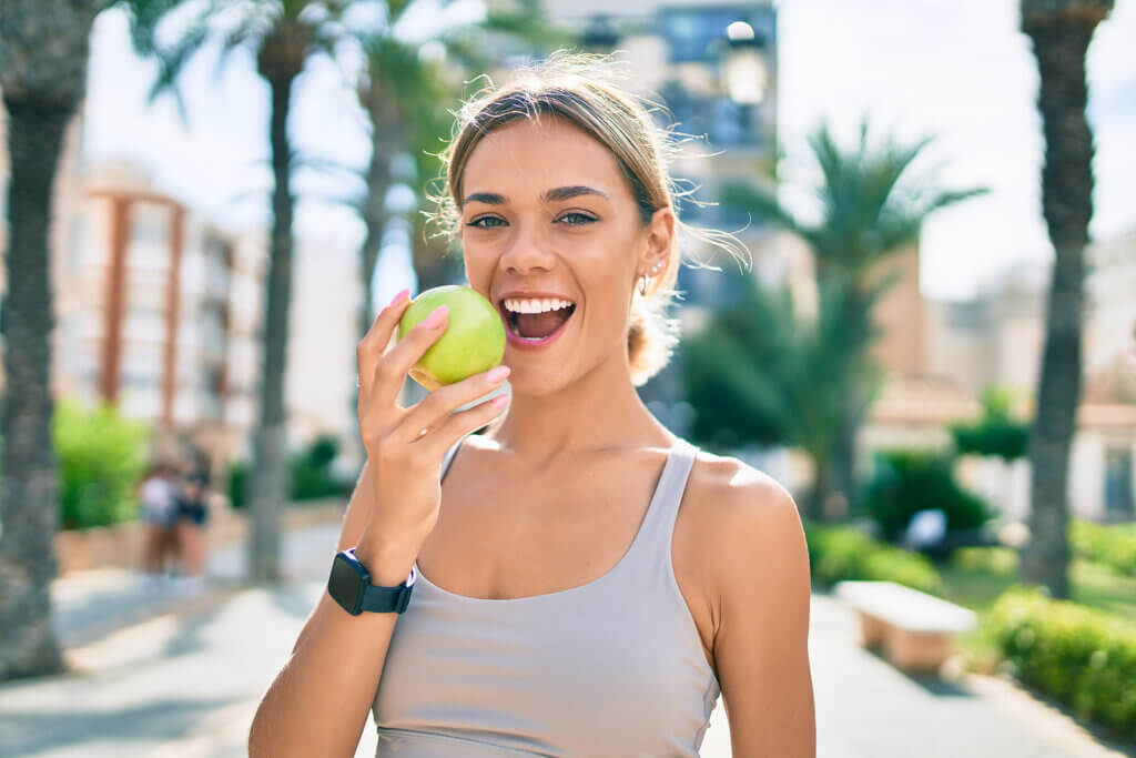 Mujer come fruta para hacer ejercicio físico.