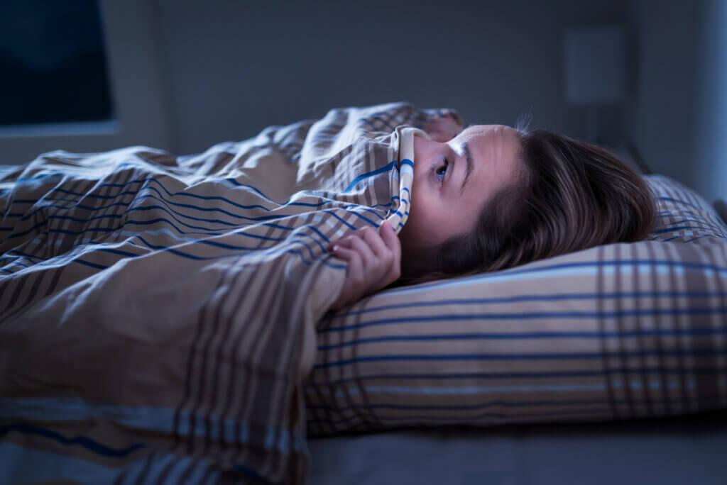 Mujer despierta con miedo a la noche.