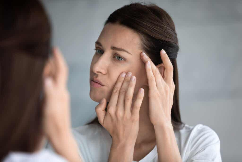 Mujer revisa su rostro por falta de colágeno.