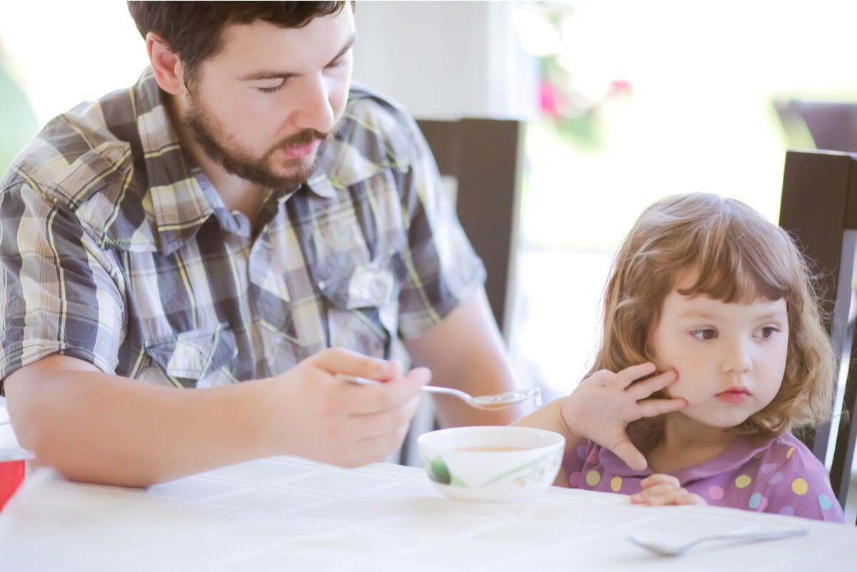 Padre intenta darle comida a hija.