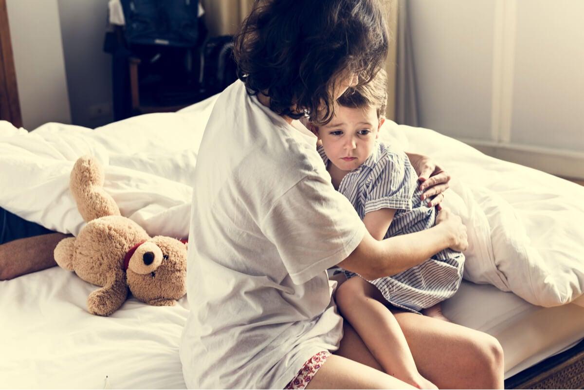 Madre consuela a un niño con pesadillas.