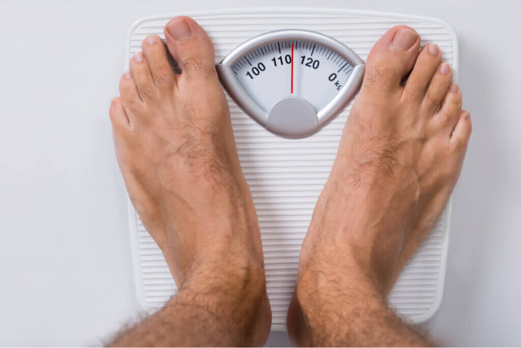 Persona de pesa en balanza casera.