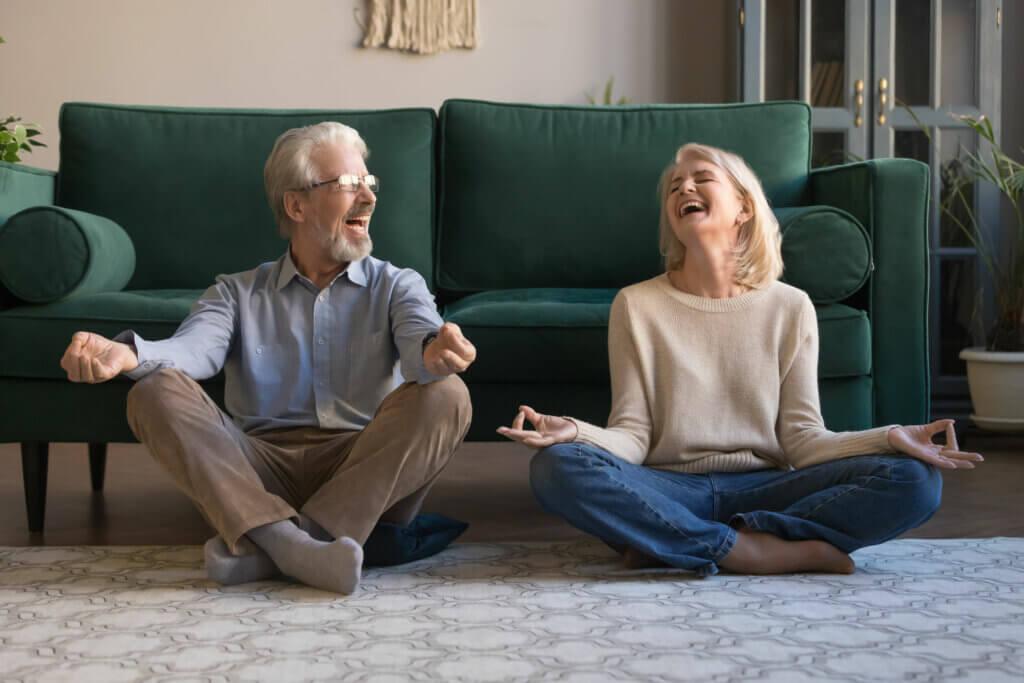 Un couple de personnes âgées qui fait de la méditation dans leur salon.