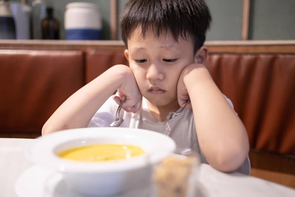 Un enfant triste devant son assiette.
