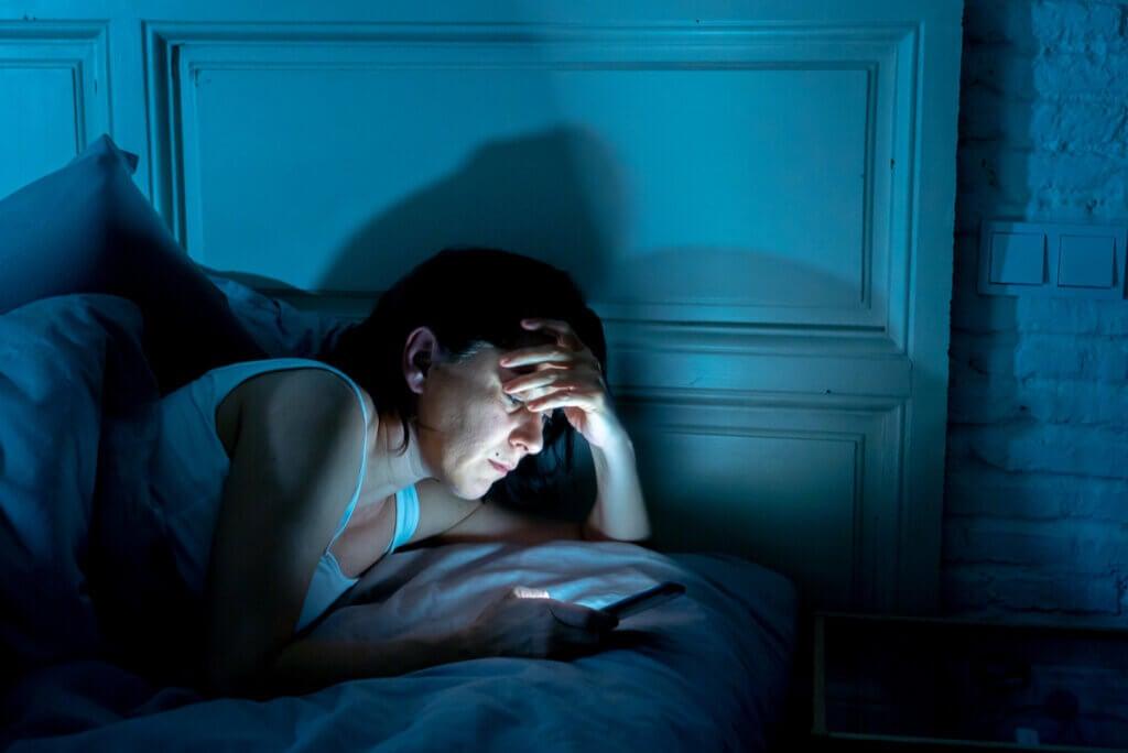 Insomnio en mujer que usa celular de noche.