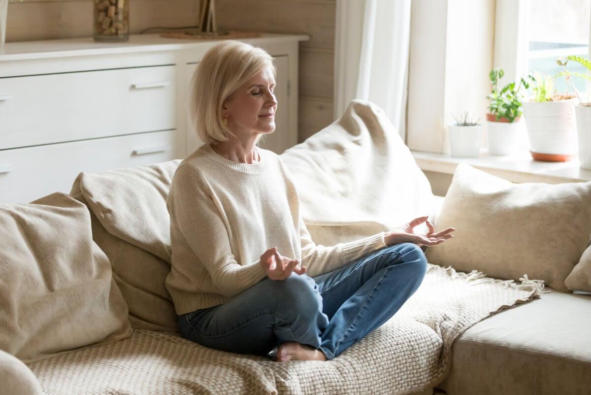 Mujer medita en su hogar.