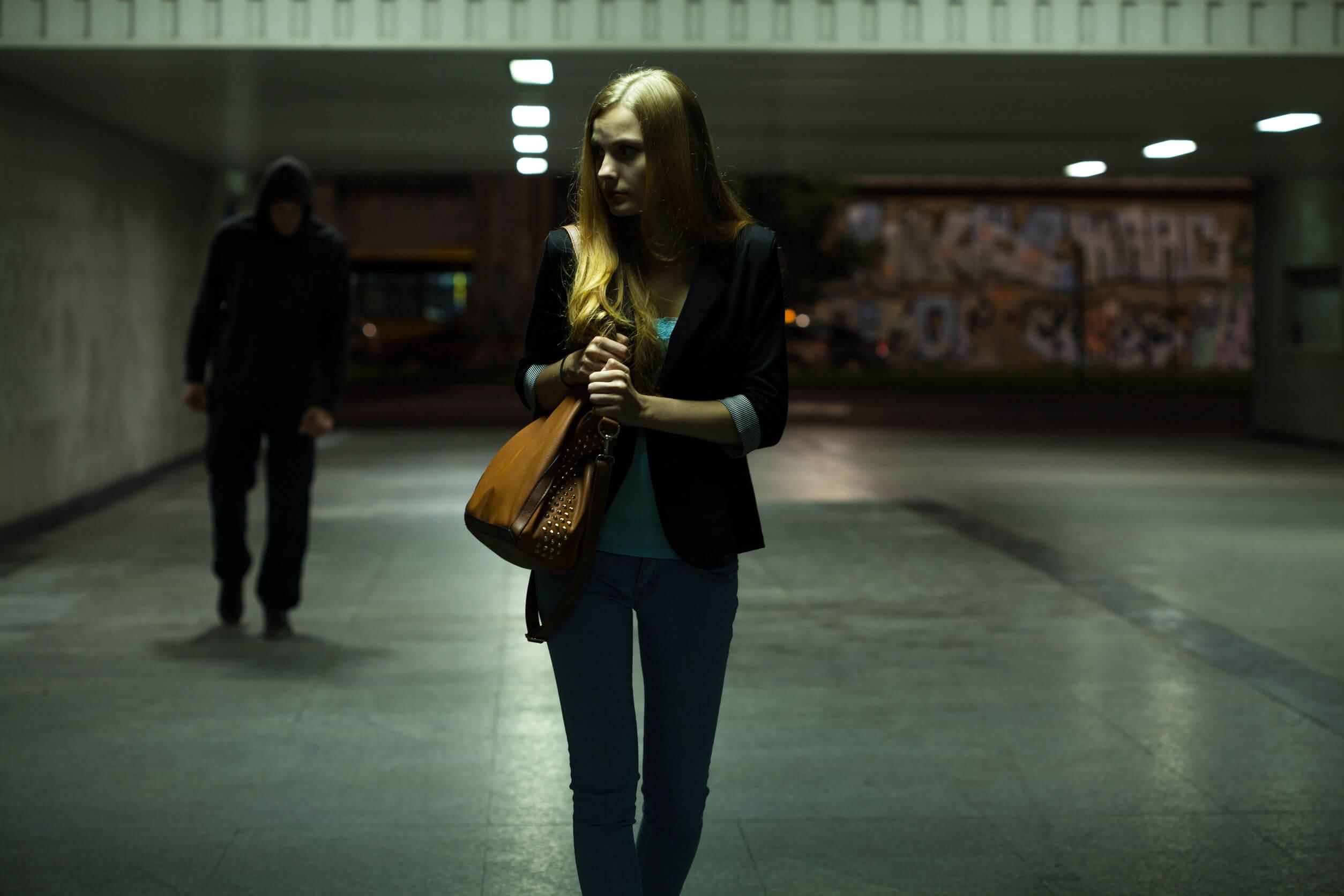 Une jeune femme dans un sous terrain suivie par un homme.