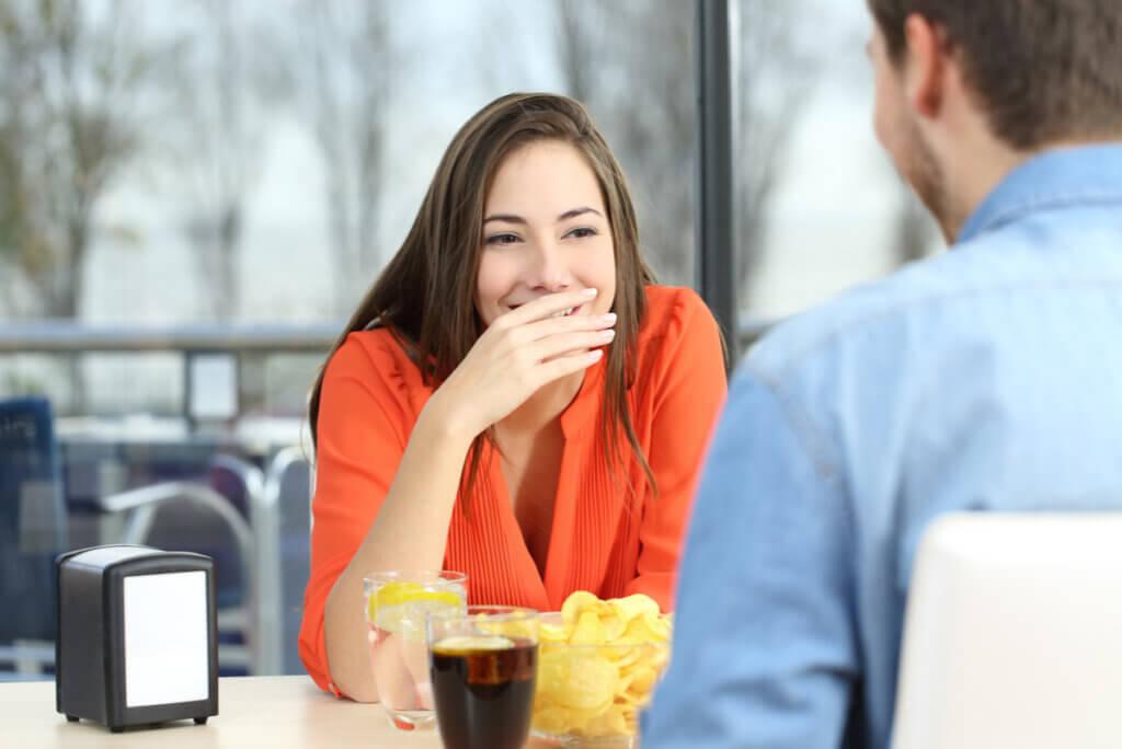 Mujer con halitosis tiene pena en una cita.