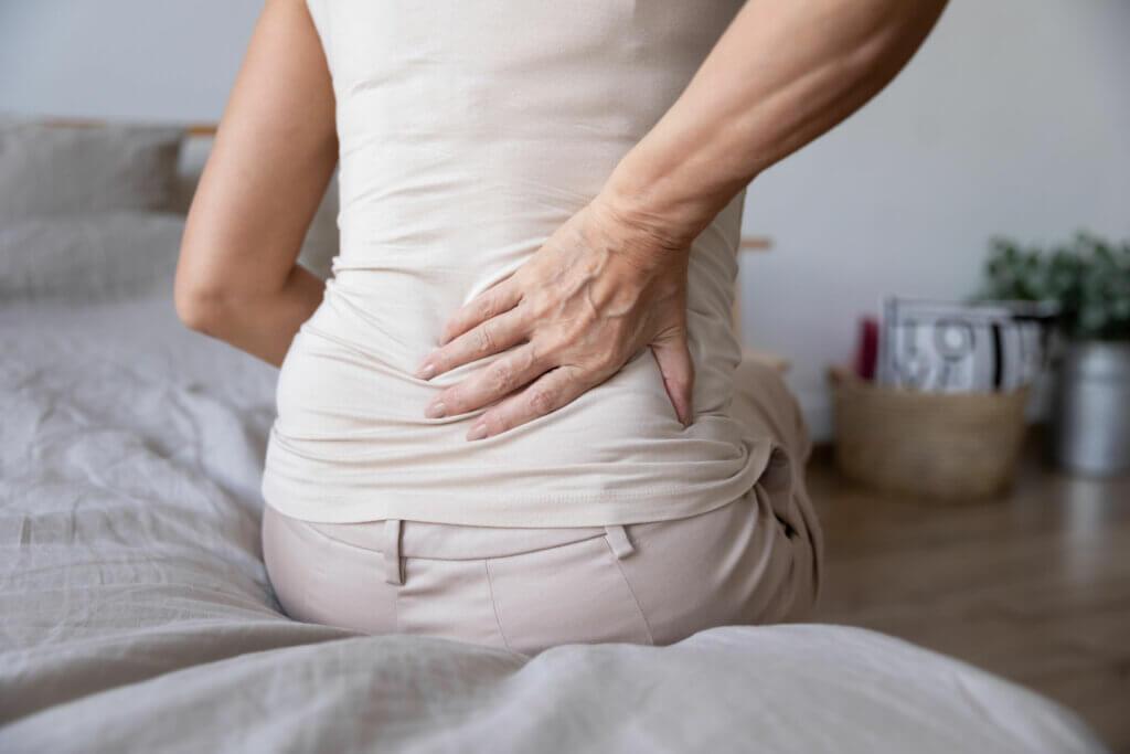 Une personne assise qui a mal au dos.