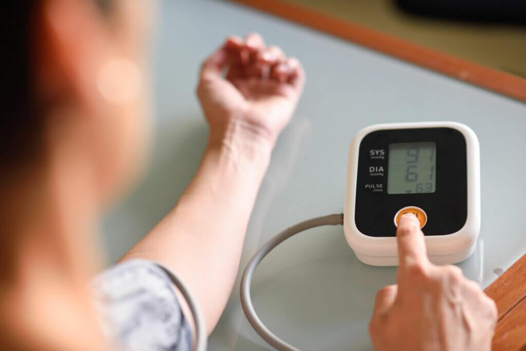 Paciente mide tensión arterial.