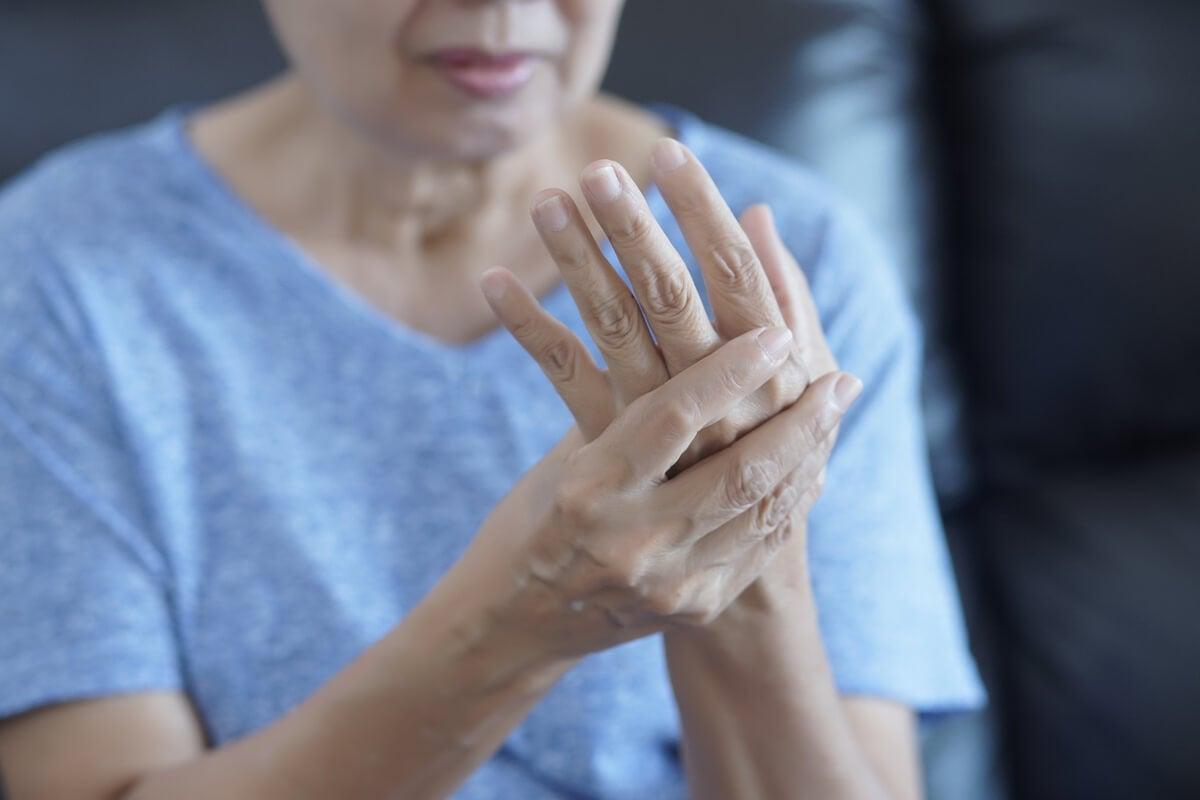 Donna con dolore alle articolazioni della mano