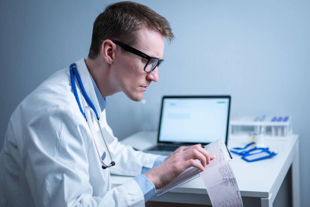 Médico revisa electrocardiograma.