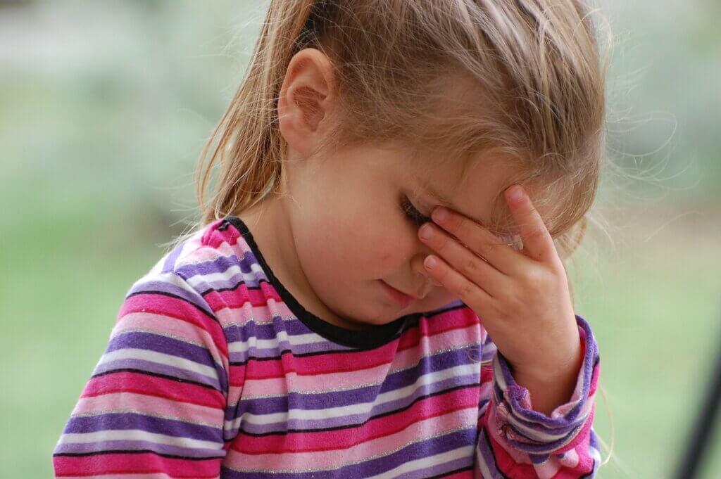 Une jeune fille qui se touche la tête.