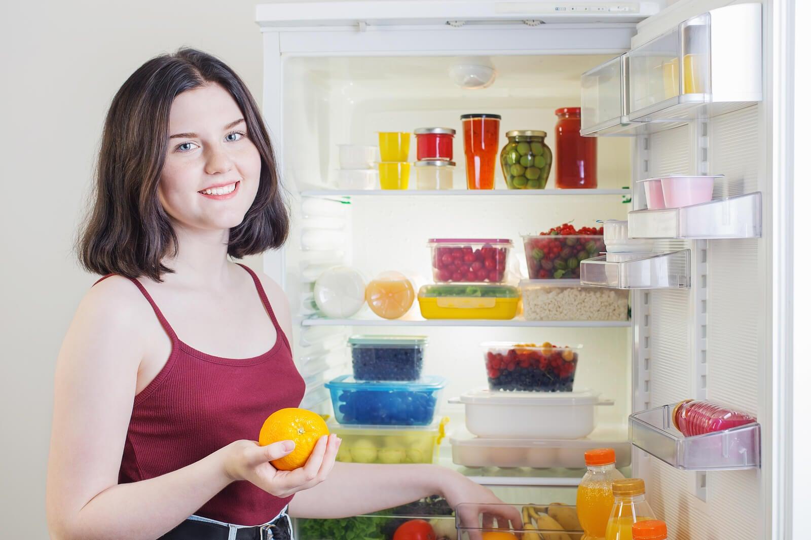 Une femme devant un réfrigérateur ouvert.